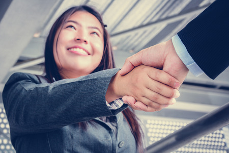Smiling businesswoman making handshake with a businessman