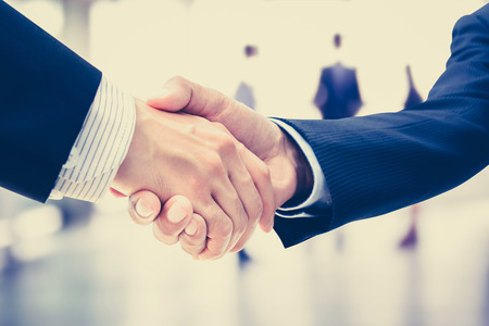 Foto de Handshake of businessmen on blur businesspeople background, vintage tone - greeting, dealing, merger and a acquisition concepts - Imagen libre de derechos