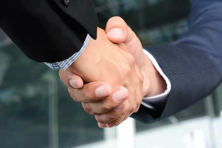 Photo pour Close up of businessman hands making handshake - greeting, dealing, merger and acquisition concepts - image libre de droit