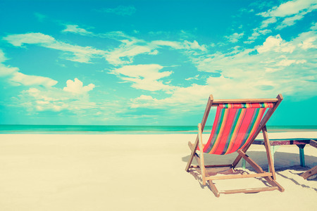 Photo pour Beach chair on white sand beach in sunny sky background, vintage tone - summer holiday concept - image libre de droit
