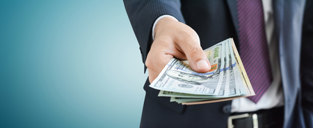 Businessman giving money,   united states dollar (USD) bills, on gray background -  panoramic financial background concept