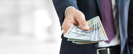 Photo pour Businessman hands giving money, US dollar bills - business and financial panoramic header background concept - image libre de droit