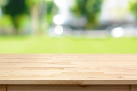 Wood table top on blurred green yard background - can be used for montage or display your products