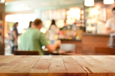 Photo pour Wood table top on blur background of coffee shop interior with some people - can be used for display or montage your products - image libre de droit