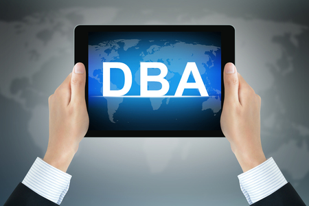 DBA (or Doctor of Business Administration) sign on computer tablet screen held by businessman hands