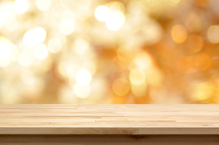 Wood table top on golden bokeh abstract background  - can be used for montage or display your products