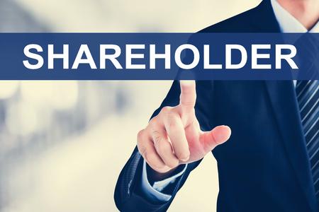 Businessman hand touching SHAREHOLDER sign on virtual screen