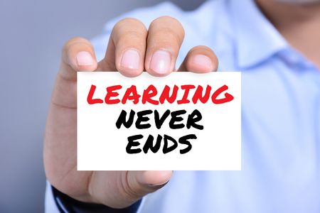 LEARNING NEVER ENDS message on the card shown by a man