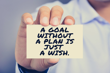 A GOAL WITHOUT A PLAN IS JUST A WISH, message on business card shown by a man