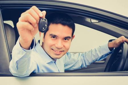 Photo pour Smiling asian man as a driver showing car key (face focused), vintage tone - image libre de droit