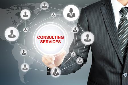 Foto de Businessman hand touching CONSULTING SERVICES sign on virtual screen - Imagen libre de derechos