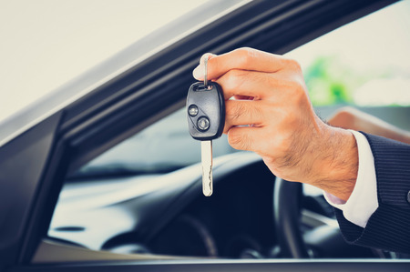 Hand holding a car key - car sale & rental business concept, vintage tone