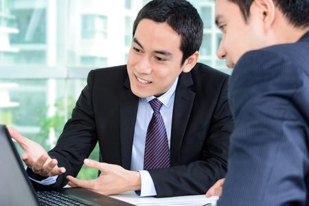 Photo pour Businessmen discussing work while looking at laptop computer - image libre de droit