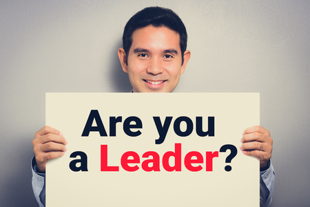 Foto de ARE YOU LEADER? message on white cardboard held by smiling man - Imagen libre de derechos