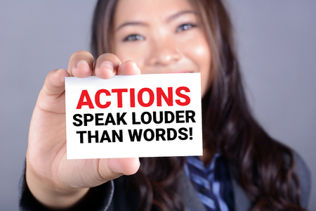 ACTIONS SPEAK LOUDER THAN WORDS, message on the card shown by a woman