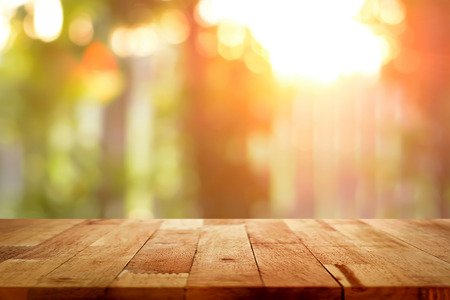 Photo for Wood table top on blur bokeh background of sunlight shining through the trees - can be used for display or montage your products - Royalty Free Image
