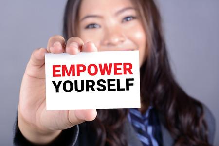 Foto de EMPOWER YOURSELF message on the card shown by a businesswoman - Imagen libre de derechos
