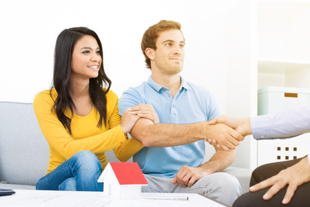 Photo pour Young couple meeting with real estate agent (or financial adviser) at home - image libre de droit