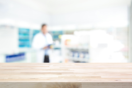 Photo pour Empty wood counter top on blur pharmacy (chemist shop or drugstore) background - image libre de droit