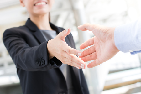 Photo for Young businesswoman going to make handshake with a businessman -greeting, dealing, merger and acquisition concepts - Royalty Free Image