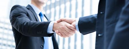 Photo pour Businessmen making handshake,  panoramic banner - image libre de droit
