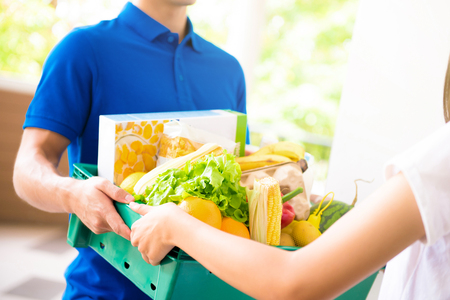 Foto für Delivery man delivering food to a woman at home - online grocery shopping service concept - Lizenzfreies Bild