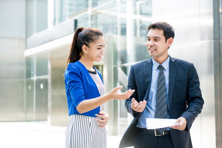 Photo for Asian business people discussing document while walking outdoors in front of office building - Royalty Free Image