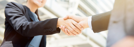 Businesswoman making handshake with a businessman, female leader concept - panoramic web bannerの写真素材