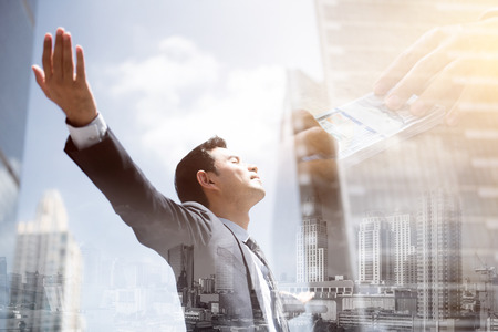 Foto de Success businessman in the city raising his arms, open palms, with face looking up - financial freedom concepts, double exposure effect - Imagen libre de derechos