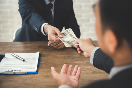 Businessman giving money, Japanese Yen,  to his partner while making contract