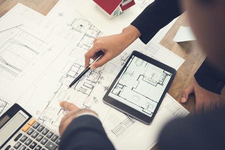 Photo pour Architects or interior designers discussing floor plan blueprints on the table - image libre de droit
