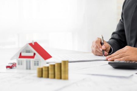 Photo pour Businessman signing document with money and house model on the table - real estate and properties financial concepts - image libre de droit
