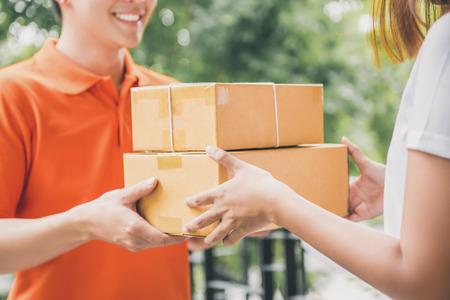 Foto de Smiling delivery man in orange uniform delivering parcel box to a woman customer - courier service concept - Imagen libre de derechos