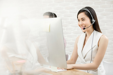 Photo pour Smiling beautiful Asian woman telemarketing customer service agent working in call center office - image libre de droit