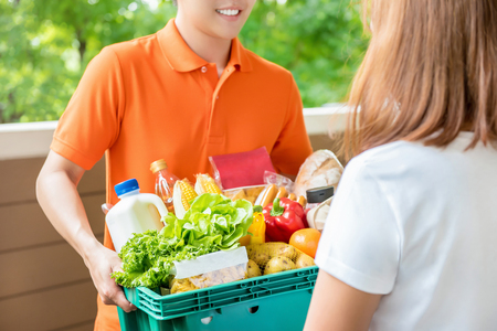 Foto für Grocery store delivery man wearing an orange polo-shirt delivering food to a woman at home - Lizenzfreies Bild