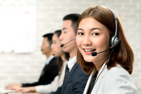 Foto de Smiling beautiful young Asian woman telemarketing customer service agent working in call center office with friendly and helpful attitude - Imagen libre de derechos