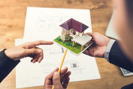 Photo pour Housing developer agent holding an architectural model and explaining concept to client or architect for real estate development. - image libre de droit