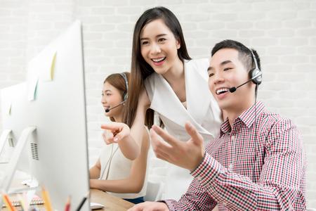 Foto de Female Asian supervisor discussing work with telemarketing customer service agent team in call center - Imagen libre de derechos