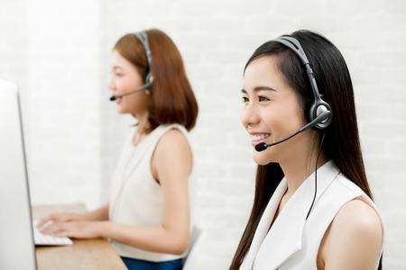Photo pour Smiling Asian woman telemarketing customer service agent team, call center job concept - image libre de droit