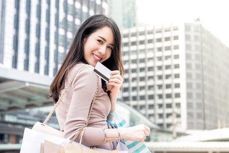 Foto de Beautiful young smiling Asian woman carrying shopping bags in her arms presenting credit card that just used for making payment - Imagen libre de derechos
