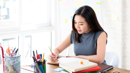 Foto de Young Asian female college student concentrating on reading book at the table preparing for examination - Imagen libre de derechos