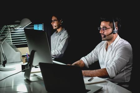 Foto de Aasian technical support customer service team working night shift in call center office - Imagen libre de derechos