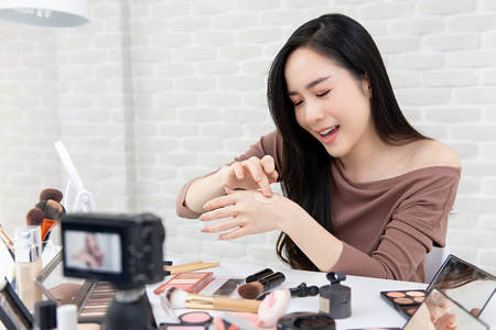 Photo pour Young beautiful Asian woman professional beauty vlogger or blogger recording cosmetic makeup product review with camera - image libre de droit