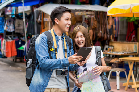 Asian couple tourist backpackers using tablet to find location while traveling on holiday in Khao San road, Bangkok, Thailandの写真素材