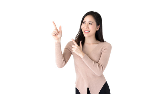Foto de Beautiful young casual Asian woman smiling and pointing hands to empty space aside, studio shot isolated on white background - Imagen libre de derechos