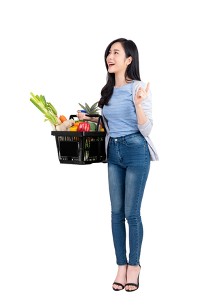 Foto de Beautiful Asian woman holding shopping basket full of vegetables and groceries, studio shot isolated on white background - Imagen libre de derechos