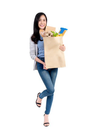Photo for Beautiful smiling Asian woman holding paper shopping bag full of vegetables and groceries, studio shot isolated on white background - Royalty Free Image