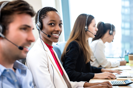 Photo pour Smiling beautiful African American woman working in call center office with diverse team as the customer care operators - image libre de droit
