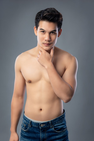 Photo pour Portrait of shirtless young handsome Asian man wearing jeans studio shot isolated on gray background - image libre de droit