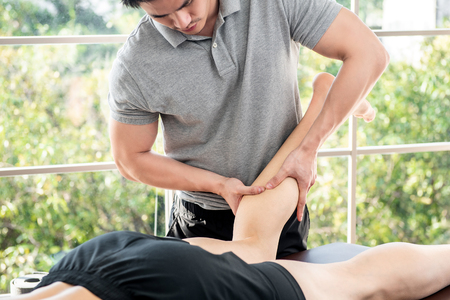 Foto de Male therapist giving leg and calf massage to athlete patient on the bed in clinic, sports physical therapy concept - Imagen libre de derechos